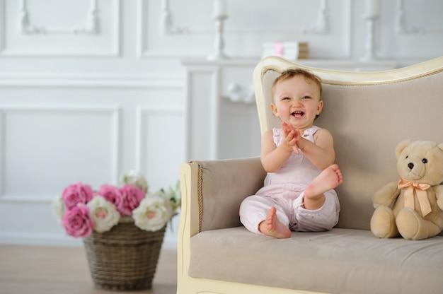 La petite fille d'un an au chapeau rouge est assise sur un canapé.