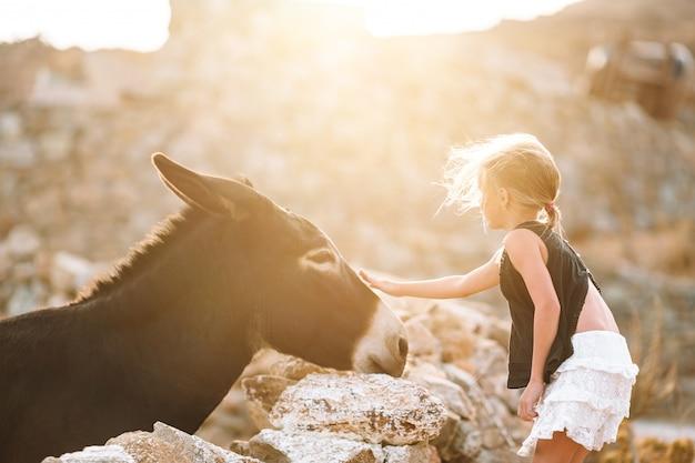 Petite fille avec un âne sur l'île de mykonos