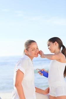 Petite fille appliquant la crème solaire sur sa mère