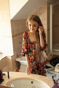 Petite fille appliquant le mascara à la salle de bains
