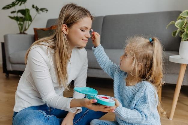 Petite fille appliquer le maquillage à la mère avec des produits cosmétiques jouets