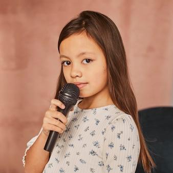 Petite fille apprenant à chanter à la maison avec microphone