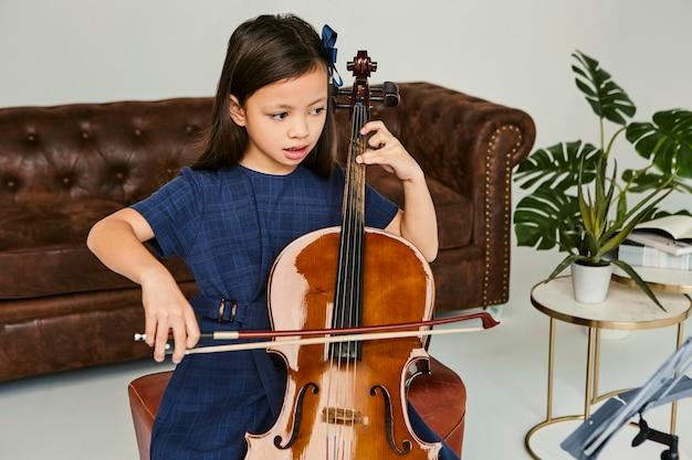 Petite fille apprenant à jouer du violoncelle à la maison