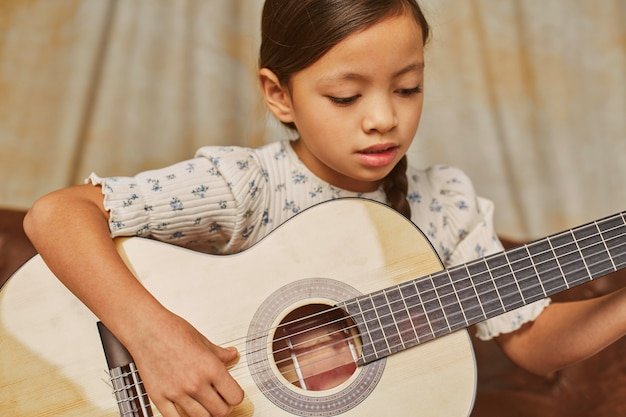 Petite fille apprenant à jouer de la guitare à la maison