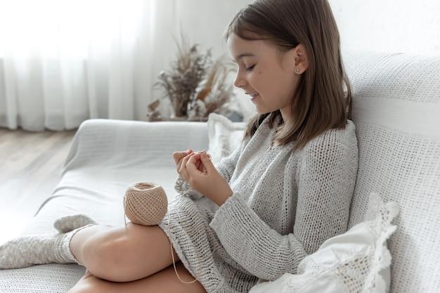 Petite fille apprenant à tricoter, concept de loisirs à la maison et de travaux d'aiguille.