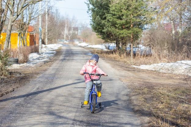 Petite fille apprend à faire du vélo avec des roues de sécurité sur la route du village