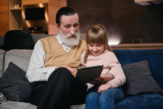 Petite fille apprend à grand-père à utiliser des appareils intelligents modernes. communication des jeunes et seniors. profitez du temps libre en famille.