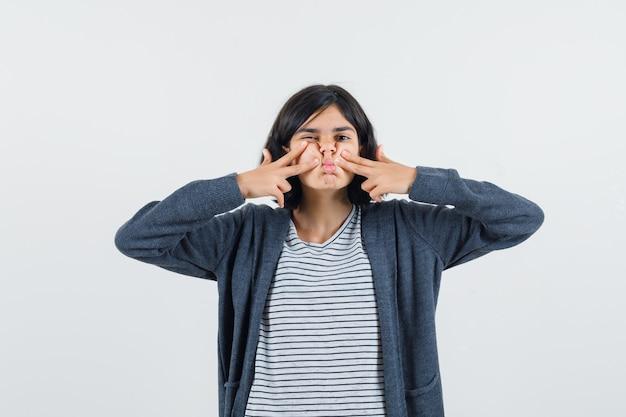 Petite fille en appuyant sur les doigts sur les joues en t-shirt, veste et à la pensif