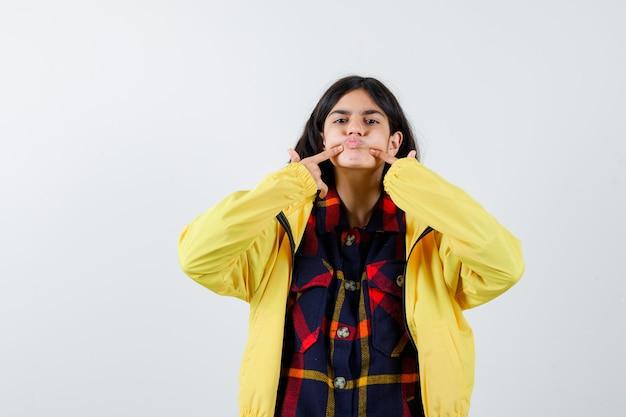 Petite fille en appuyant sur les joues avec le doigt en chemise à carreaux, veste et à mignon