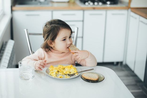 Petite fille l'après-midi dans la cuisine de lumière blanche dans un pull rose mangeant une omelette