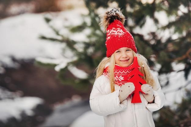 Une petite fille avec un arbre de noël rouge dans ses mains en hiver dans la rue.