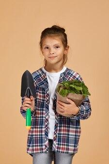 Petite fille, arrosage des plantes dans un pot de fleur