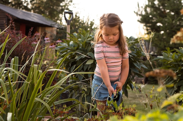 Petite fille arrosant les plantes dans le jardin en été à la campagne