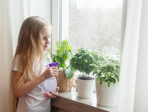 Petite fille arrosant des plantes d'intérieur dans sa maison