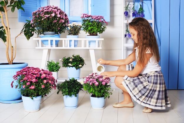 La petite fille arrosant des pots de fleurs.