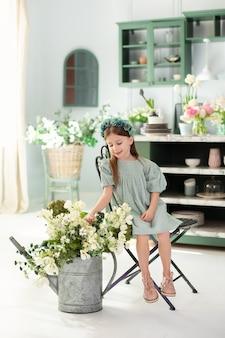 Petite fille avec arrosoir et fleurs d'été dans la cuisine