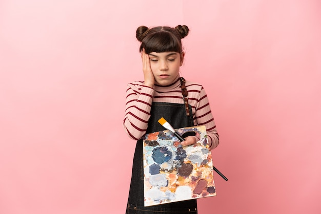 Petite fille artiste tenant une palette isolée sur rose avec des maux de tête
