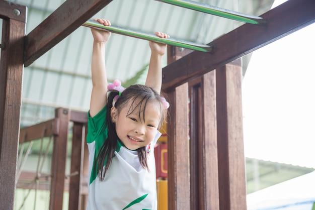 Petite fille asiatique accrochant bar dans la cour d'école