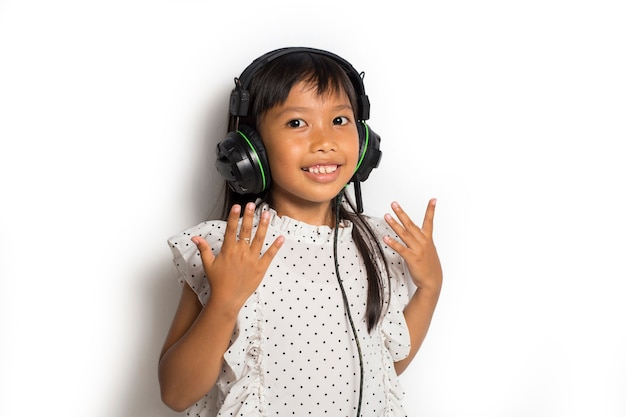 Petite fille asiatique, appréciant la musique. danser et bouger exprimant de vraies émotions positives