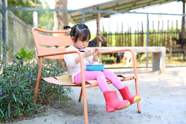 Petite fille asiatique assis sur une chaise en plein air dans la ferme avec de la nourriture végétale pour un animal.
