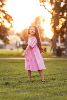 Petite fille asiatique aux cheveux longs marchant dans le parc