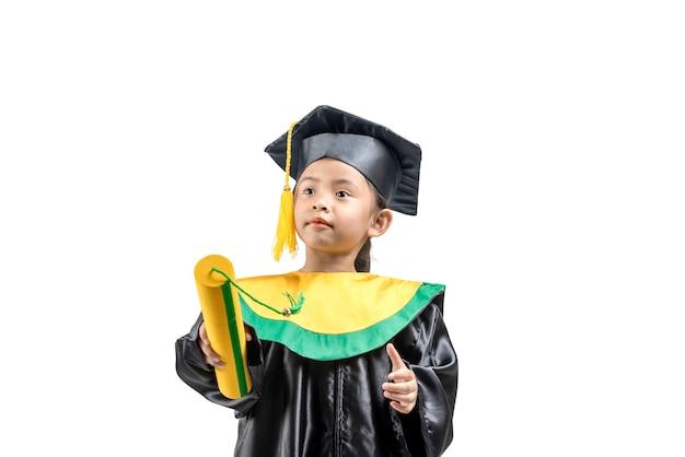 Petite fille asiatique en chapeau et robe de graduation détenant un certificat
