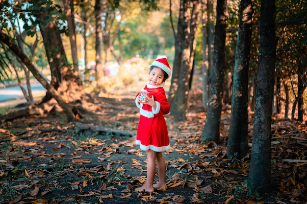 Petite fille asiatique en costume de père noël rouge avec présent fort dans le parc