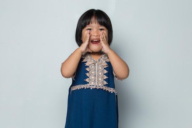 Petite fille asiatique criant et criant annonçant isolé sur fond blanc