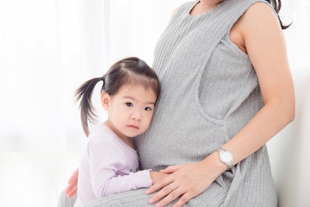 Petite fille asiatique debout avec sa mère enceinte et faire face sérieuse