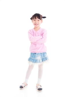 Petite fille asiatique debout et sourit sur fond blanc