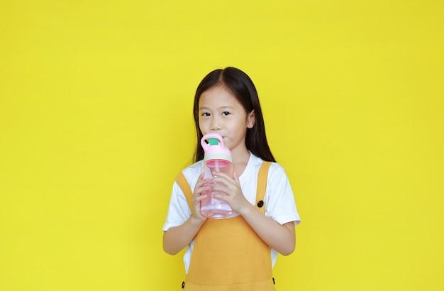 Petite fille asiatique eau potable sur fond jaune