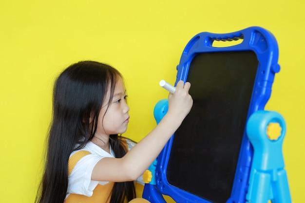Petite fille asiatique écrit sur tableau noir vide