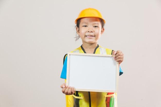 Petite fille asiatique ou enfants en chemise bleue et casque jaune debout et tenant le tableau blanc à la main
