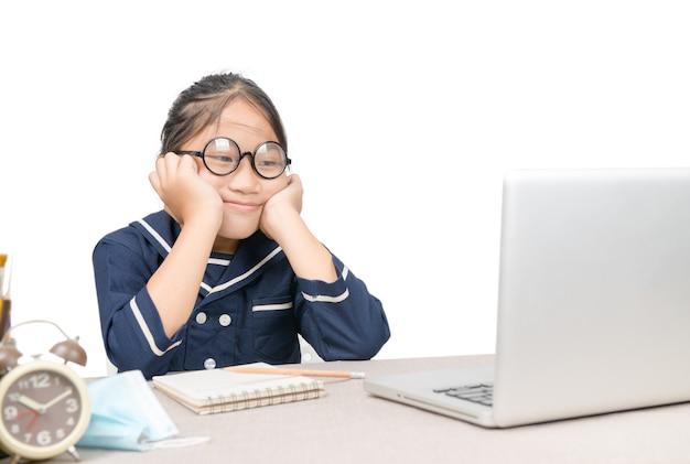 Petite fille asiatique à faire ses devoirs sur ordinateur portable