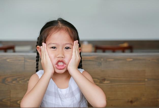 Petite fille asiatique avec grimace d'expression allongé sur la table en bois avec regarder la caméra.