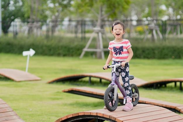 Petite fille asiatique heureuse faire du vélo au terrain de jeux