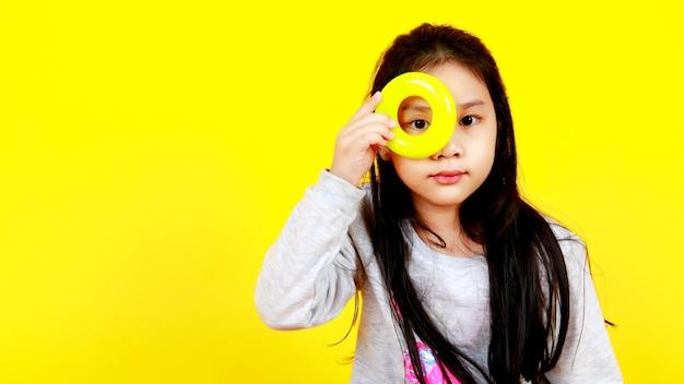 Une petite fille asiatique intelligente sur un pull a mis une bande circulaire en plastique sur un joli visage et aime regarder à travers le trou central comme innocent intéressant et douter de voir via la forme de l'anneau. jeu amusant pour observer le jouet