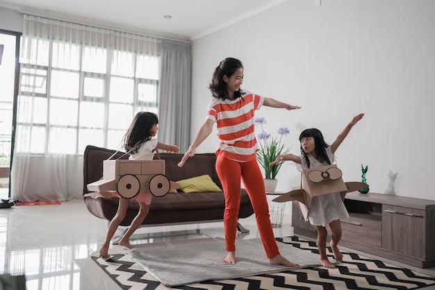 Petite fille asiatique jouant avec un avion jouet en carton avec sa mère à la maison