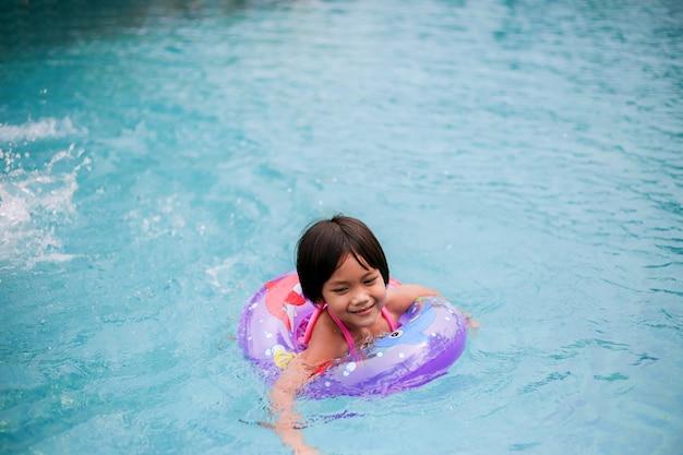 Petite fille asiatique jouant dans la piscine