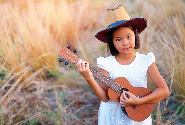 Petite fille asiatique jouant du ukulélé et porte un chapeau brun