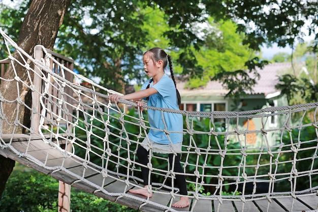 Petite fille asiatique jouant sur un pont en bois suspendu