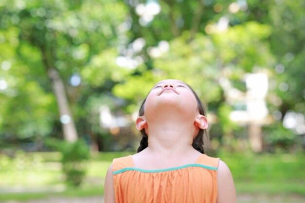 Petite fille asiatique lève les yeux au ciel