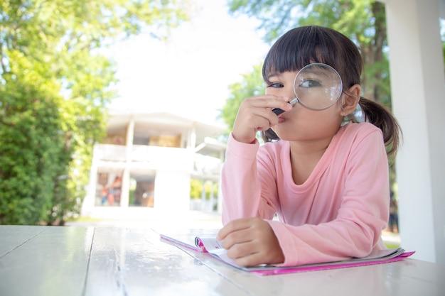 Petite fille asiatique lisant les livres sur le bureau avec une loupe