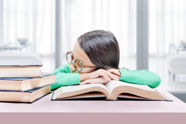 Petite fille asiatique avec des lunettes allongé sur le livre sur la table. retour au concept de l'école