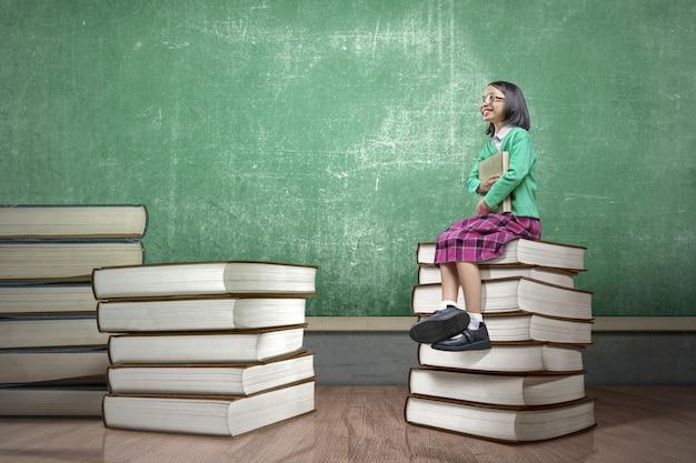 Petite fille asiatique avec des lunettes assis sur la pile de livres