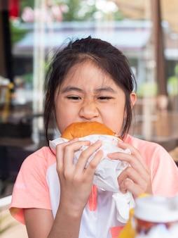 Petite fille asiatique mangeant un hamburger. les enfants asiatiques mangent du hamburger au fromage de poulet.