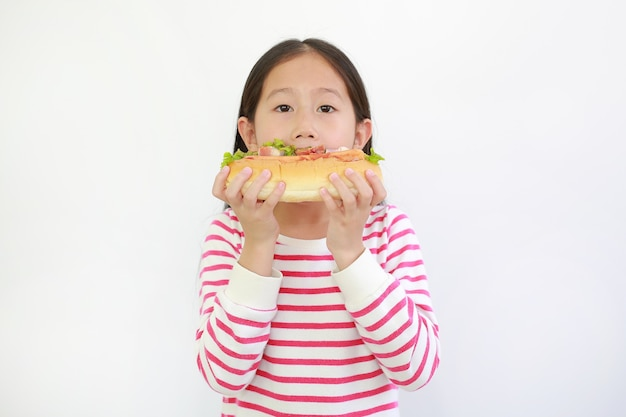 Petite fille asiatique mangeant un hot dog isolé sur fond blanc