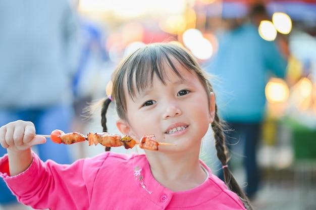 Petite fille asiatique marchant dans la rue de bangkok, acheter un barbecue et manger de la nourriture de rue en soirée