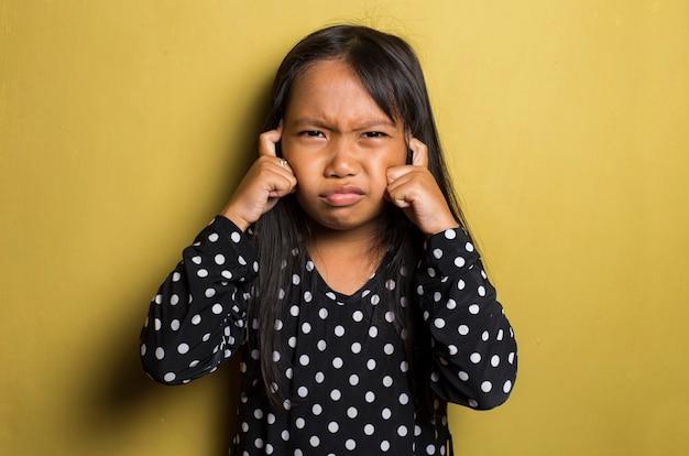 Petite fille asiatique avec maux de tête et problèmes