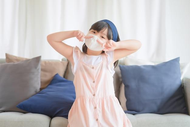 Une petite fille asiatique mignonne portant un masque hygiénique pour prévenir le coronavirus ou l'épidémie de covid-19 maintient la distance sociale et reste à la maison.